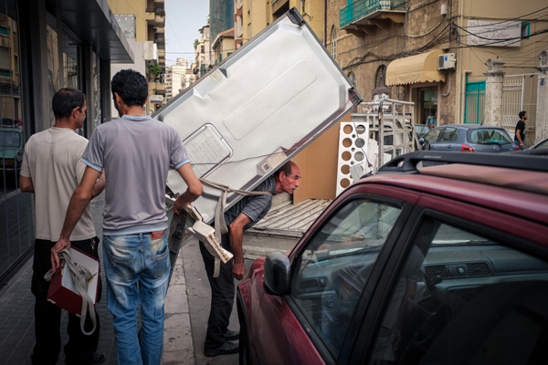An old man walking with refrigerator, working as furniture mover. Gemmayzeh Street, Beirut. © Nour El Refai