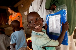 Young boy shows excitement for mosquito net. © Trevor Clark